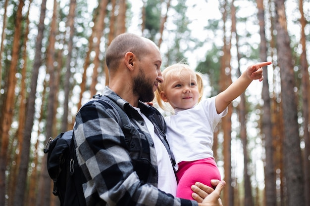 Papà tiene il bambino tra le braccia durante le escursioni nei boschi. escursione in famiglia in montagna o nella foresta.