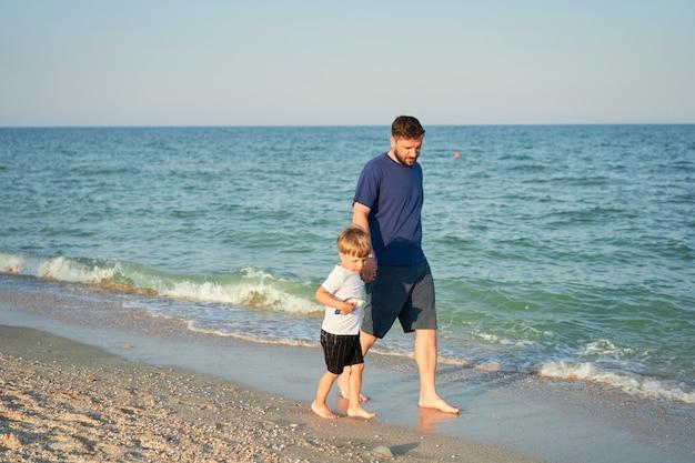 Papà tiene la mano del figlio. padre figlio di trascorrere del tempo insieme vacanza al mare giovane ragazzino a piedi spiaggia. infanzia felice con papà.