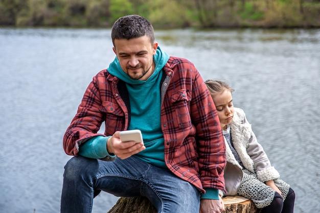 Papà sta controllando il suo telefono, senza prestare attenzione a sua figlia, per una passeggiata nel bosco.