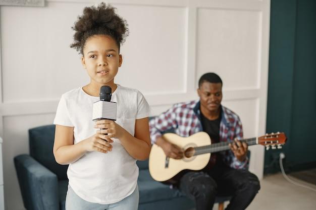 Papà è seduto con una chitarra e una figlia con un microfono