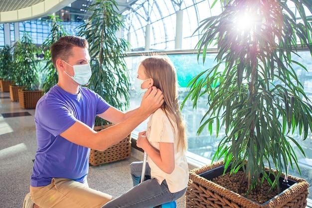 Papà e bambina con maschere mediche all'aeroporto. protezione contro il coronavirus