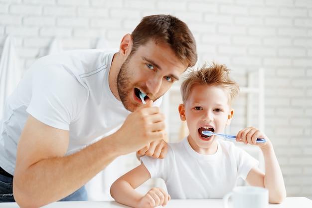 Papà e figlio piccolo lavarsi i denti insieme in bagno