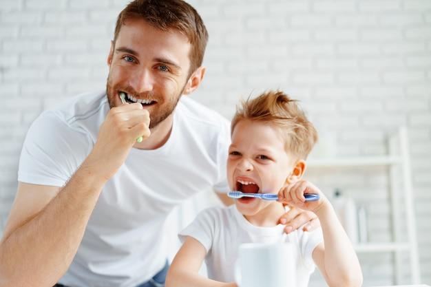 Papà e figlio piccolo lavarsi i denti insieme