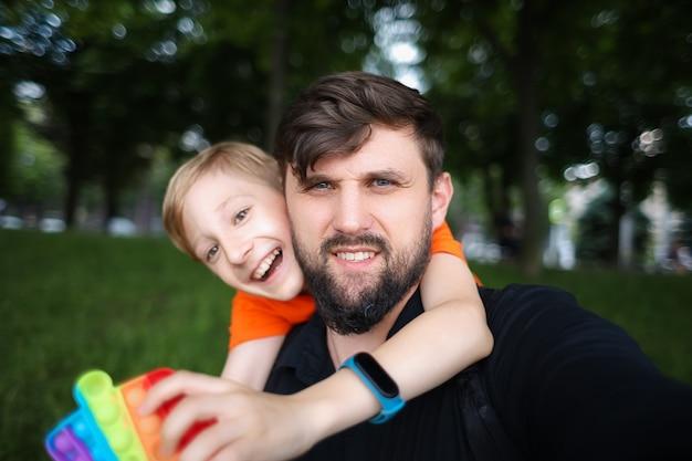 Papà guarda la telecamera e si fa un selfie il bambino lo abbraccia da dietro per il collo e ride allegramente