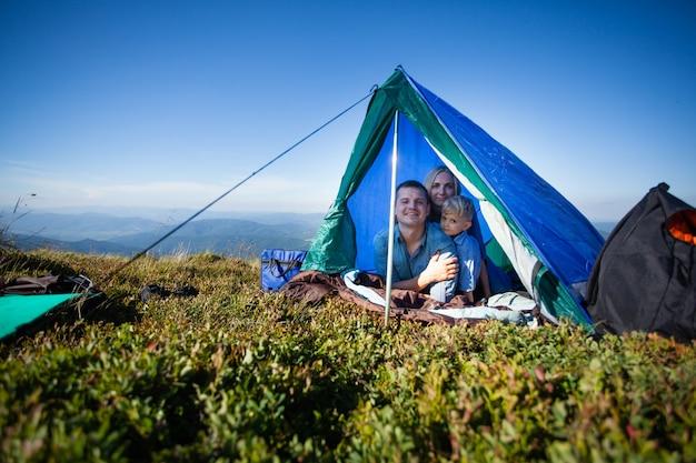 Papà, mamma e figlio che guardano fuori dalla tenda durante un viaggio in montagna