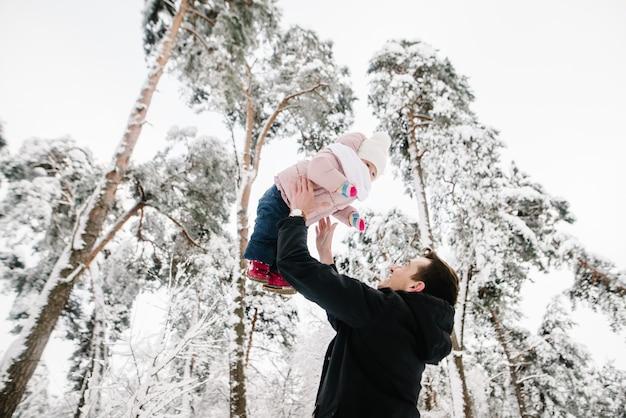 Papà che gioca e vomita la figlia nel parco della foresta invernale.
