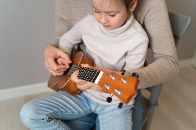 Papà suona la chitarra con sua figlia. il bambino impara a suonare uno strumento musicale con un tutor. duetto musicale di un padre con un bambino.
