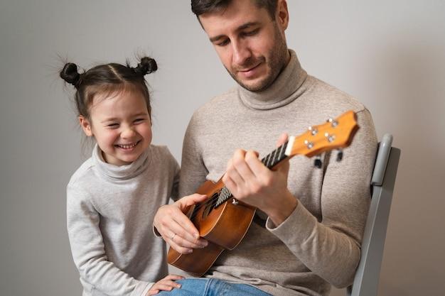 Papà suona la chitarra con sua figlia.