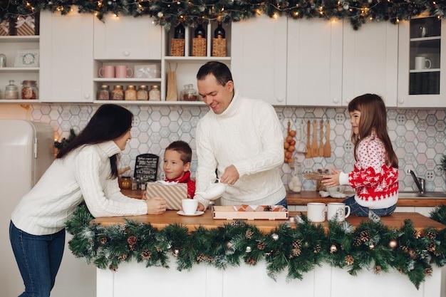 Papà che versa il tè mentre figlia che tiene i biscotti e mamma che parla al figlio