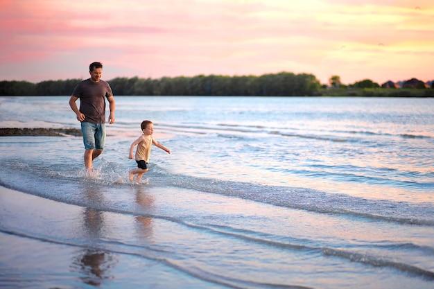 Papà corre dietro a suo figlio lungo la riva del fiume al tramonto
