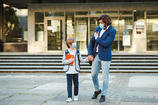 Papà e scolaro che indossa la maschera per il viso. ritorno a scuola durante la pandemia di coronavirus.