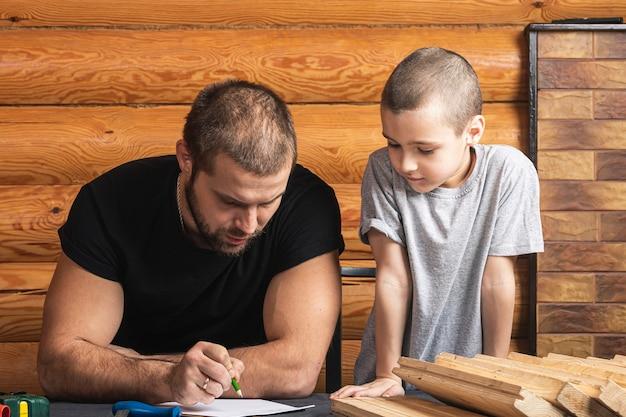 Papà e figlio stanno disegnando su carta, pianificando come costruire una casetta per uccelli, strumenti e una trave sul tavolo del laboratorio