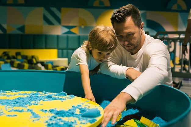Papà e figlio sono appassionati del processo creativo con la sabbia cinetica nel centro di sviluppo. sviluppo delle capacità motorie fini. alleviare lo stress. comprensione e sostegno reciproci.