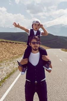 Papà e figlio in giubbotti neri e berretto che camminano sulla strada asfaltata sullo sfondo del monte everest