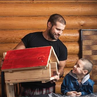 Papà e figlio hanno raccolto e dipinto la casetta per gli uccelli e sono molto contenti del loro lavoro