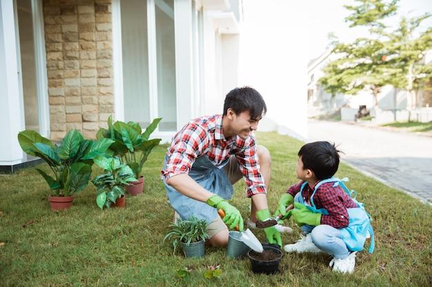 Papà e figlio che piantano insieme una pianta che fa il giardinaggio a casa loro