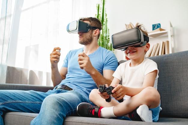 Papà e figlio che si siedono sul divano e giocano insieme con gli occhiali vr