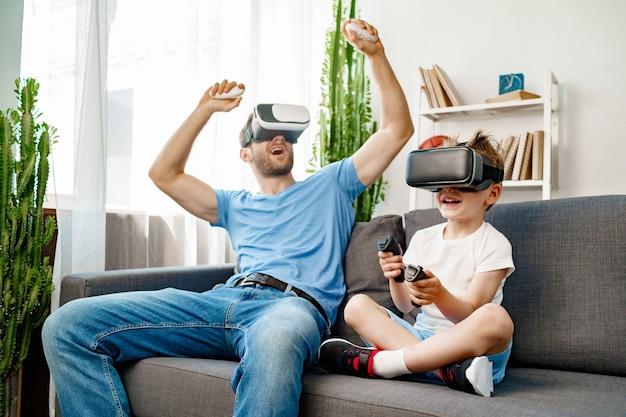 Papà e figlio che si siedono sul divano e giocano con gli occhiali vr