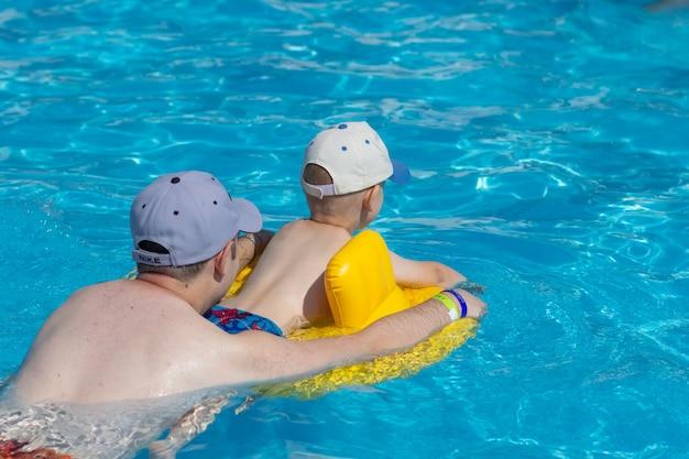 Papà e figlio nuotano in piscina su un cerchio gonfiabile giallo. vacanze estive in famiglia