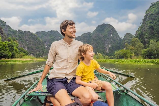 Papà e figlio turisti in barca sul lago tam coc ninh binh viet nam è patrimonio mondiale dell'unesco