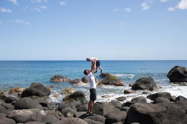Papà e figlio che camminano lungo la riva dell'oceano. fine settimana al mare. una pietra da spiaggia.
