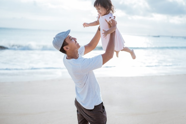 Papà che fa oscillare in aria la figlia piccola sulla spiaggia divertendosi insieme