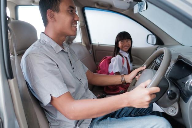 Papà porta sua figlia a scuola la mattina guidando un'auto. alunno delle elementari asiatico torna a scuola