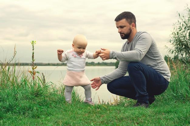 Papà insegna alla figlia a camminare, parcheggiare, natura. camminare sull'erba. padre e figlia. primi passi.