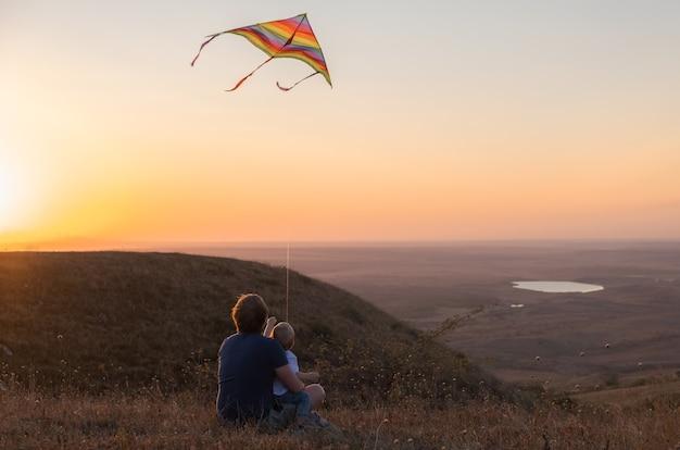 Papà e figlio del ragazzo del bambino fanno volare un aquilone al tramonto.