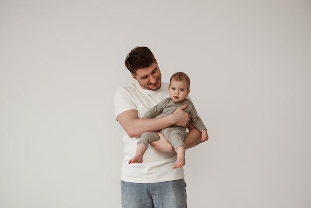 Papà con una maglietta bianca tiene in braccio un bambino piccolo, la ammira, il bambino guarda nella telecamera. ritratto di famiglia di papà e figlia su sfondo bianco.