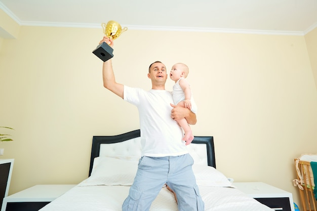 Papà con un bambino che tiene una tazza chempionship super papà con un bambino il concetto di genitori e infanzia