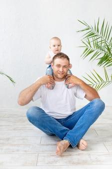 Papà con il figlio al collo che si diverte su uno sfondo bianco, paternità felice e famiglia, festa del papà
