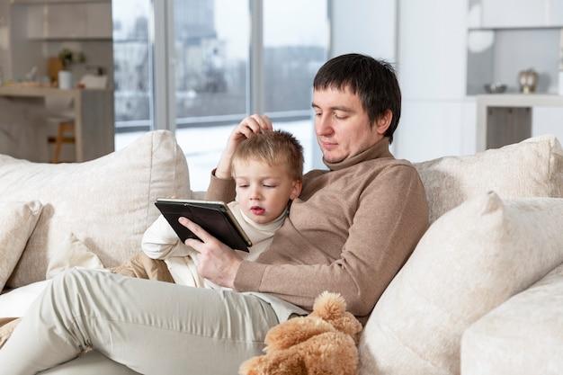 Papà con suo figlio piccolo è seduto sul divano con un tablet. trascorrere del tempo insieme. amore, tenerezza e rapporti familiari.