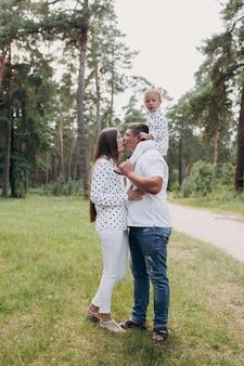 Papà porta una bambina sulle spalle nel parco, foresta. il concetto di vacanza estiva. papà, mamma, festa del bambino. trascorrere del tempo insieme. aspetto familiare. coppia che bacia