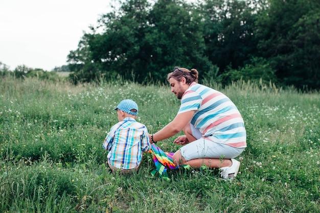 Papà con un bambino in età prescolare che raccoglie aquiloni volanti