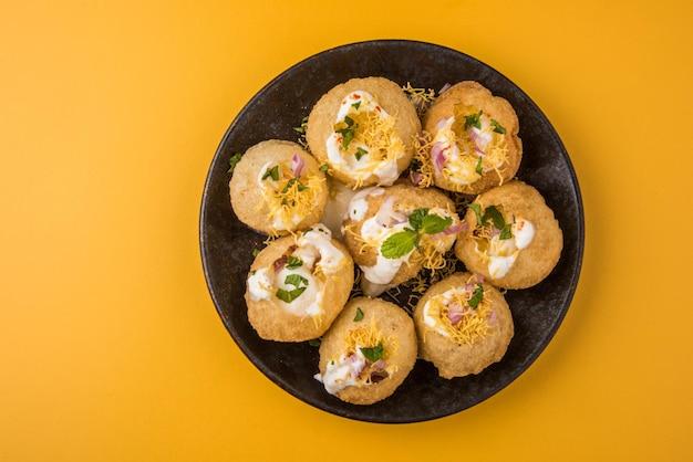Dahi puri è uno snack popolare nello stato del maharashtra, in india. questo piatto rientra nella categoria chat. servito in un piatto rotondo su sfondo colorato o in legno. messa a fuoco selettiva