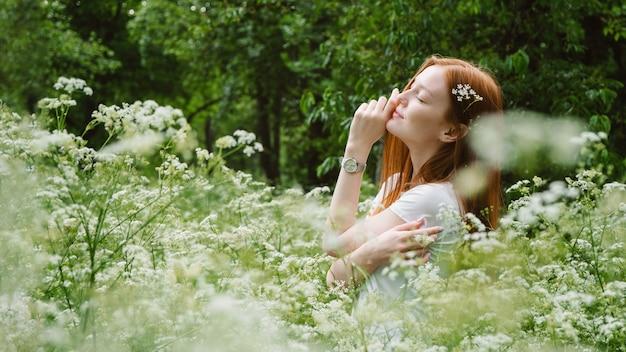 Affermazioni quotidiane, miglioramento della vita, potere della positività. le braccia sorridenti della giovane donna si sono alzate, godono della natura, celebrando la libertà sul fondo dell'albero verde. emozioni umane positive.