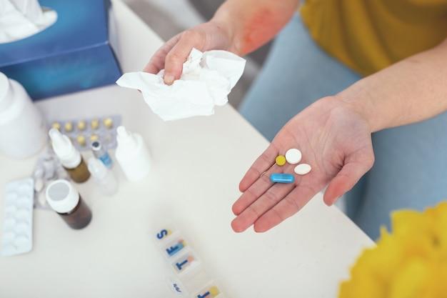 Dose giornaliera. paziente che tiene con cura le pillole prescritte su un tavolo bianco per non lasciarle cadere