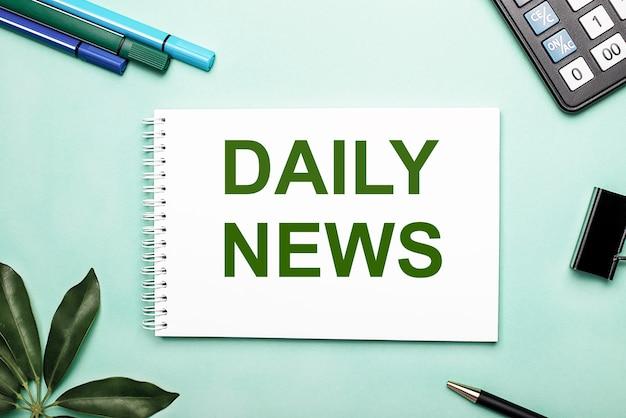 Notizie giornaliere è scritto su un foglio bianco su una parete blu vicino alla cancelleria e al foglio scheffler. chiamare all'azione. concetto motivazionale