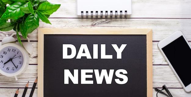 Notizie giornaliere scritte su un tavolo nero vicino a matite, uno smartphone, un blocco note bianco e una pianta verde in una pentola