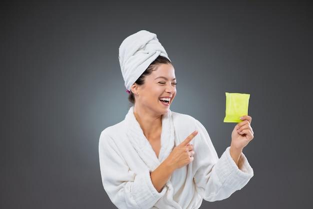 Tamponi giornalieri per le mestruazioni. la donna in accappatoio e asciugamano indica un assorbente. tiene in mano un assorbente femminile che assorbe un oggetto che una donna indossa durante le mestruazioni. protezione contro il sanguinamento