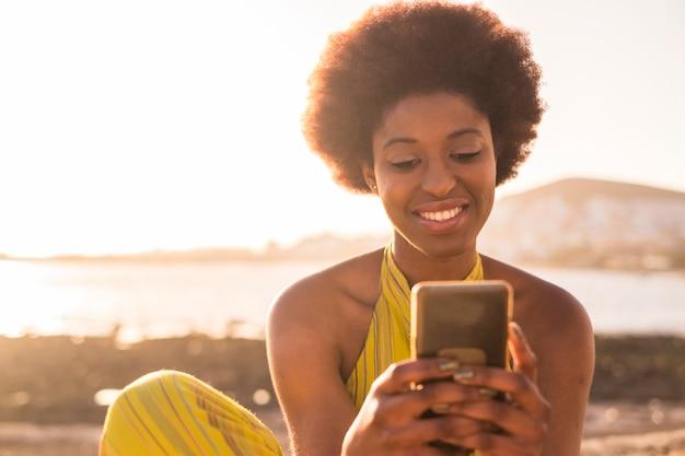 Scena sunnny estiva quotidiana con bella ragazza afroamericana di razza nera con capelli alternativi che guarda il telefono e controlla il concetto di vacanza sulla spiaggia di luce dorata e sole sui social media