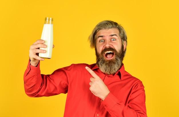 Latticini da latte per adulti e bambini. bicchiere regalo contadino felice. l'uomo barbuto beve latte utile. adoro i baffi al latte. concetto di cibo e bevande. utilità del latte dito puntato.