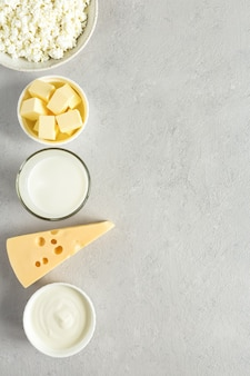 Prodotti lattiero-caseari latte formaggio burro panna acida vista dall'alto su cemento grigio sfondo con copia spazio