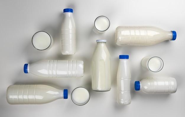 Confezionamento di prodotti lattiero-caseari, raccolta di bottiglie e bicchieri con latte e panna isolato su bianco