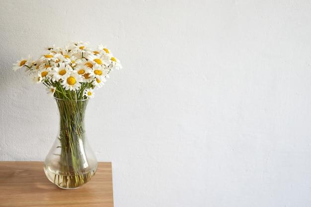 Mazzo dei fiori della margherita in vaso di vetro che rimane sul bordo di legno. interno di casa.