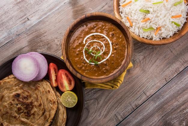 Dal makhani o daal makhni, pranzo o cena indiano servito con riso semplice e burro roti o chapati o paratha e insalata