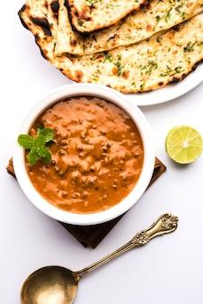 Dal makhani o daal makhni è un alimento popolare del punjab, in india, realizzato con lenticchie nere intere, fagioli rossi, burro e panna e servito con naan all'aglio o pane indiano o roti