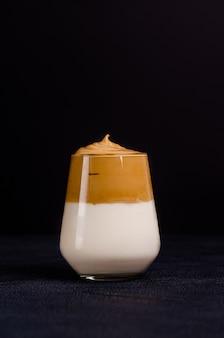 Caffè dalgon in una tazza di vetro su uno sfondo nero. copia spazio, piatto laici, spazio per il testo. avvicinamento.