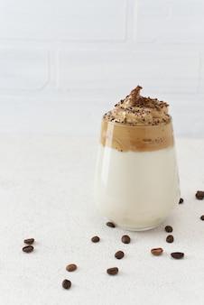 Caffè dalgona in vetro con chicchi di caffè intorno con spazio di copia